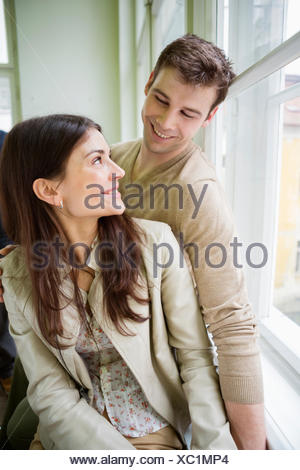 Happy romantic couple looking at each other at home - Stock Photo
