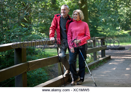 A mature couple standing on a footbridge in the countryside - Stock Photo