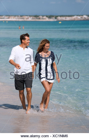 Couple walking on beach holding hands, ankles deep in water - Stock Photo