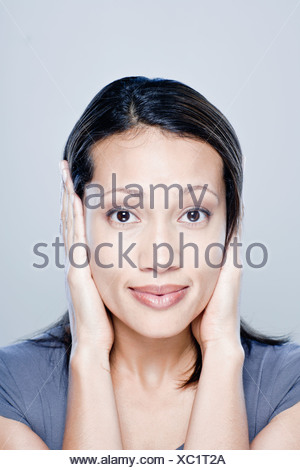 Portrait of young woman with hands covering ears, studio shot - Stock Photo