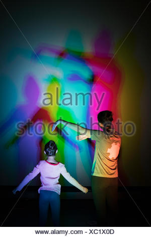 Scientist and girl casting multicolor shadows on projection screen in science center theater - Stock Photo