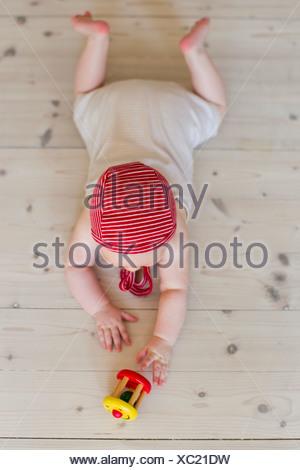 Baby girl lying on floor with toy - Stock Photo