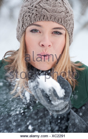 Woman blowing handful of snow - Stock Photo