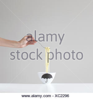 hand holding a forkful of spaghetti over a bowl - Stock Photo