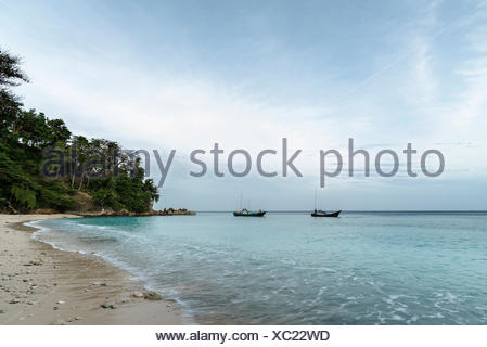 Two fishing boats in a small lagoon on the beach of the Fantastically nice island Pulau woe in Indonesia. - Stock Photo