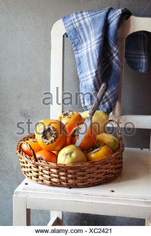 Still life with quince and persimmon on a rattan tray - Stock Photo