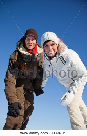 Young couple wearing ski wear, smiling at camera - Stock Photo