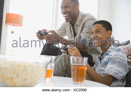 Father and son playing video games at home - Stock Photo