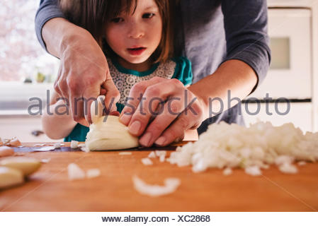 Mother teaching her daughter to chop onions