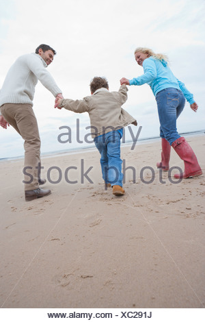 Family Running Along Winter Beach - Stock Photo