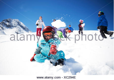 Young boy throwing snowball whilst friends play behind him - Stock Photo