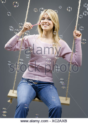 Portrait of a young woman sitting on a rope swing and blowing soap bubbles - Stock Photo
