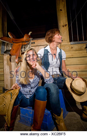 Mother and teenage daughter wearing boots and cowboy hat in horse stable - Stock Photo