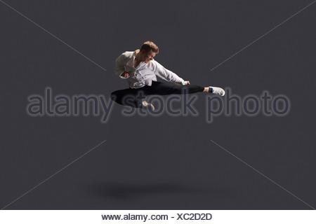 Studio shot of young man mid air practicing martial arts