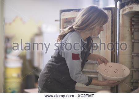 Female potter putting bowl in workshop kiln - Stock Photo