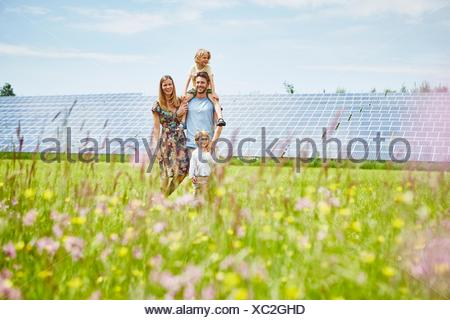 Young family, walking through field next to solar farm - Stock Photo