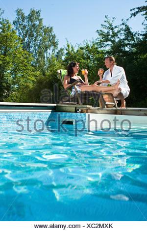 Couple drinking near swimming pool - Stock Photo