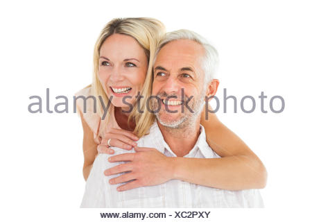 Happy man giving his partner a piggy back - Stock Photo