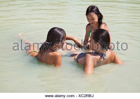 Mother and two girls play in a lake - Stock Photo