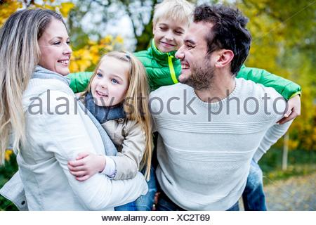 MODEL RELEASED. Parents carrying their children in autumn, laughing. Stock Photo