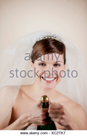 A young bride opening a bottle of champagne - Stock Photo
