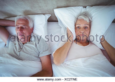 Wife blocking ears with pillow while husband snoring on bed - Stock Photo
