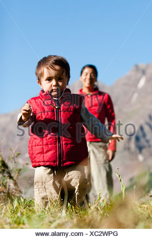 Mother watches 14 month old son explore meadow taking break on backpacking trip. Maroon Bells Snowmass Wilderness Aspen Colorado - Stock Photo