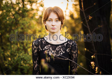 Finland, Southwest Finland, Portrait of young woman in forest - Stock Photo