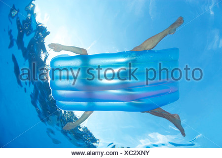 Man on inflatable lilo in pool - Stock Photo