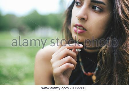 Woman with nose ring chewing grass looking away - Stock Photo