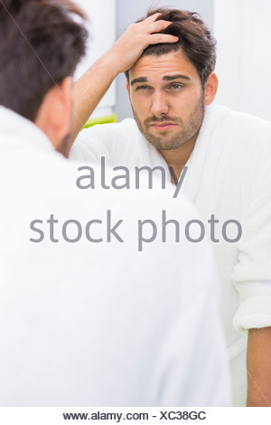 Reflection of man suffering from headache in mirror - Stock Photo