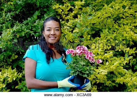 Portrait of mature woman with flowering pot plant in garden - Stock Photo