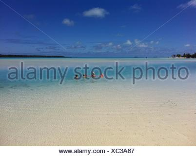 Mother and three children swimming in sea - Stock Photo