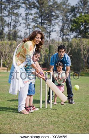 Family playing cricket in a lawn, Gurgaon, Haryana, India - Stock Photo
