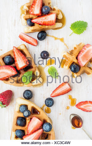 Home made Belgian waffles served on a white woodenl tray with berries , marple syrup and mint leaves, top view - Stock Photo