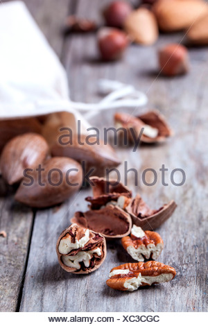 Whole and chopped pecan nuts on old wooden table. - Stock Photo