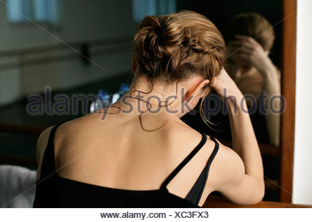 Exhausted female ballet dancer sitting in front of a mirror - Stock Photo