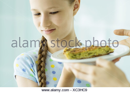 Girl making face at piece of quiche - Stock Photo