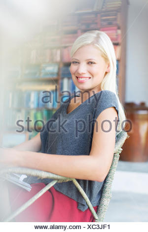 Woman smiling in armchair - Stock Photo