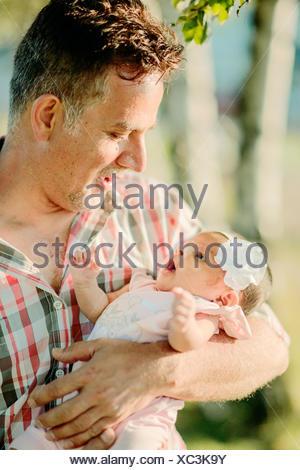 Sweden, Vastra Gotaland, Gothenburg, Grandfather holding little girl (6-11 months) - Stock Photo