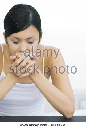 Woman holding up cup to face, eyes closed - Stock Photo