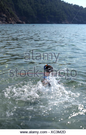 Boy splashing about in the sea wearing a snorkel and mask, Thassos, Greece - Stock Photo