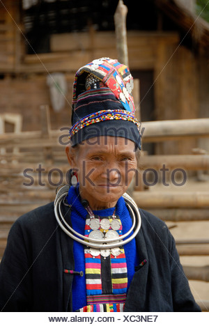 Portrait of old woman of the Akha Loma ethnic group, traditional black costume, colourfully embroidered, cap, silver neck ring - Stock Photo