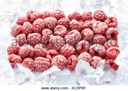 Frozen raspberries surrounded by ice cubes - Stock Photo