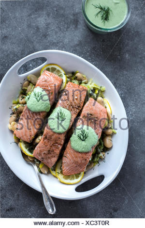 A plate white butter beans topped with oven baked salmon slices is photographed from the front view. photographed from the top ( - Stock Photo
