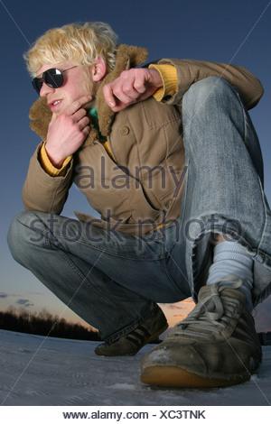doubtfully young man crouching - Stock Photo