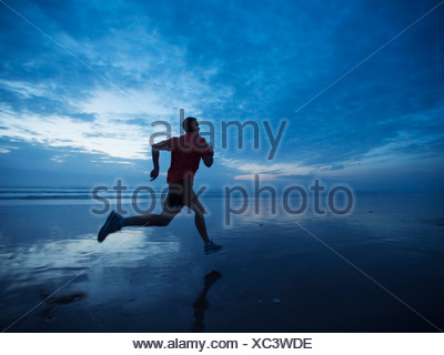 USA, Oregon, Rockaway Beach, Man running along beach - Stock Photo