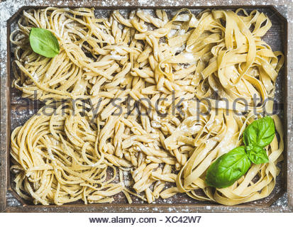 Various homemade fresh uncooked Italian pasta with flour and green basil leaves in wooden tray, top view, horizontal composition - Stock Photo