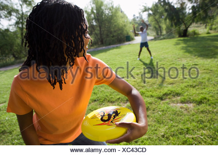 Woman playing frisbee with daughter 11 13 in park smiling focus on foreground tilt - Stock Photo