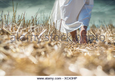 Young woman walking in field - Stock Photo
